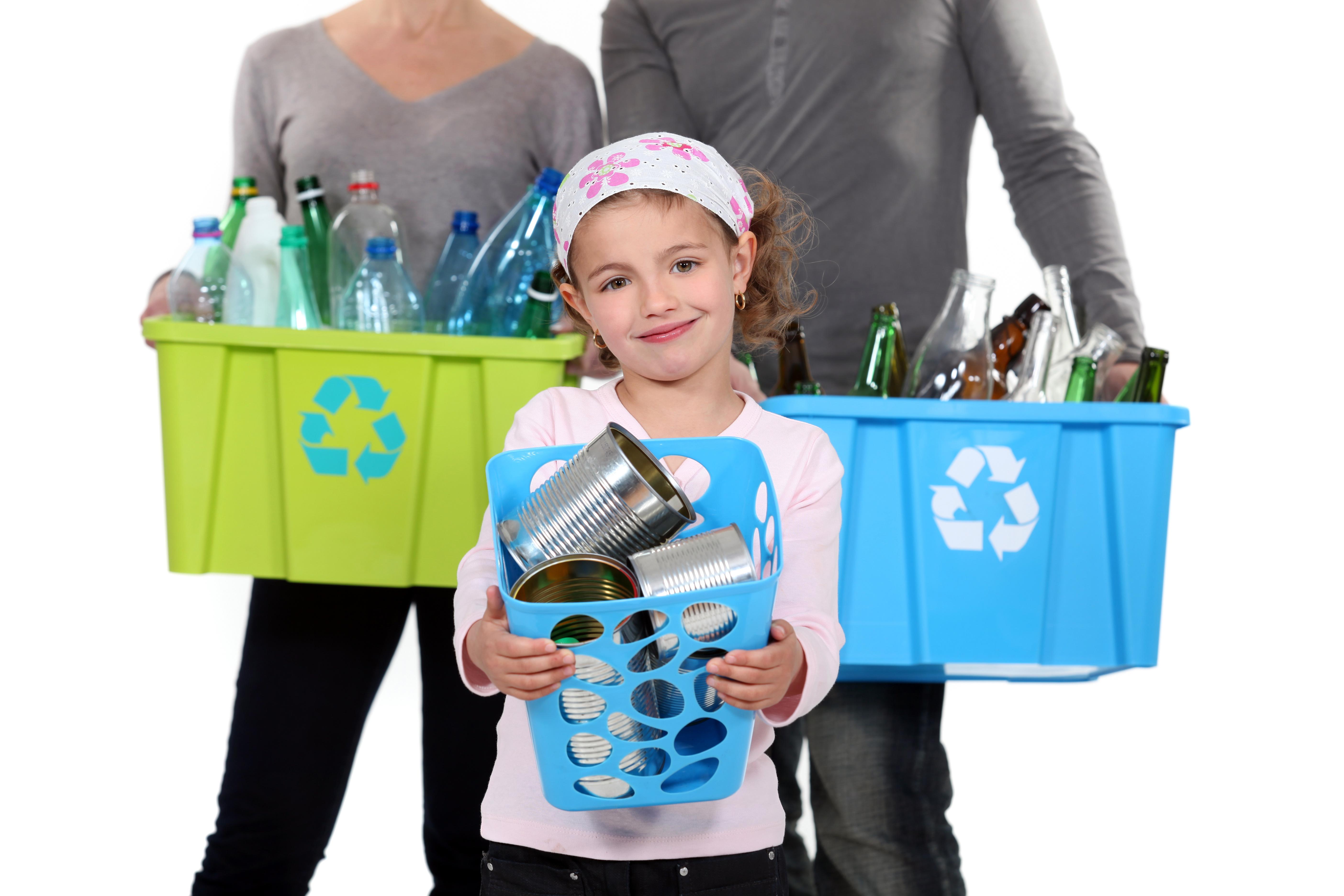 Ludzie trzymający kartony z materiałami poddanymi recyklingowi jako działanie zapobiegające powstawaniu zanieczyszczeń