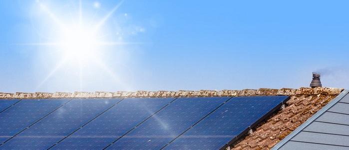 Bateria słoneczna na dachu budynku oraz słońce na nie padające